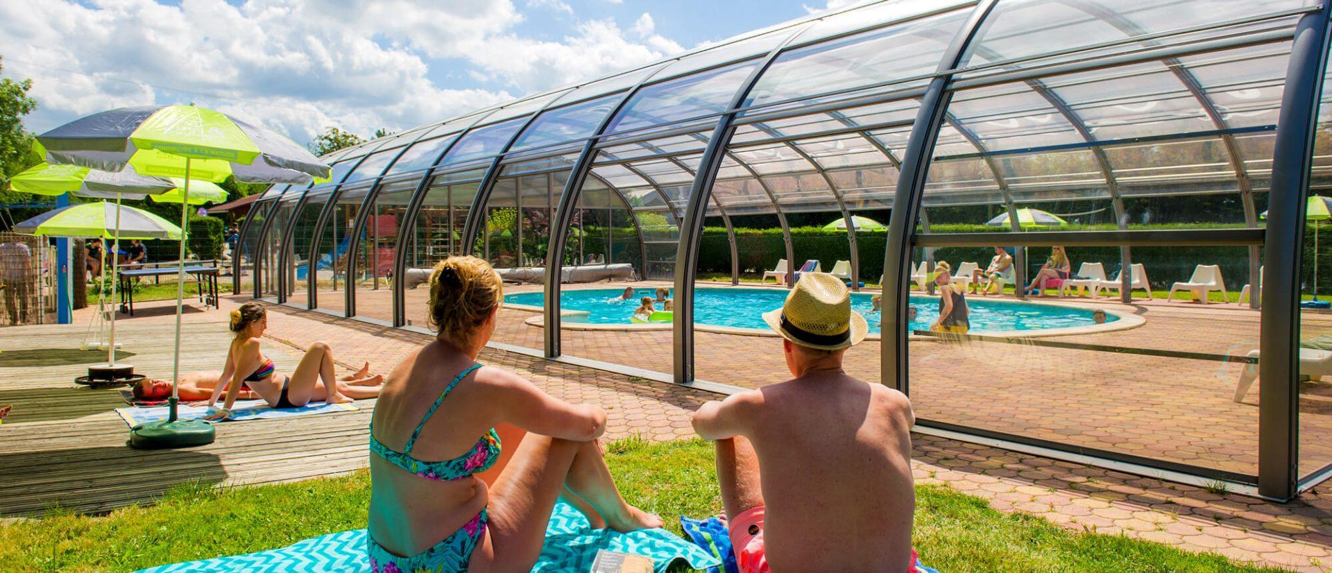 Panorama de personnes au solarium avec vue sur la piscine couverte du Clos de la Chaume un camping Piscine Couverte dans les Vosges