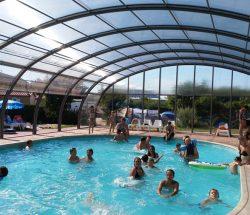vue de la piscine couverte avec du monde au camping avec piscine a corcieux, le clos de la chaume