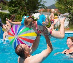 Famille jouant dans la piscine du camping avec piscine dans les Vosges, au clos de la Chaume à Corcieux